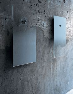 Fiction  Design:Jean-Marie Massaud  Series of mirrors available in two different sizes, realized in extralight glass with degrading shaded silvering, hanging on the wall with a chromium-plated metal cylinder. The small mirror can have a degrading shade upwards or downwards…