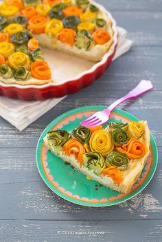 La torta salata con rose di verdure porta in tavola i colori della primavera, un guscio croccante che racchiude un bouquet di sapori. Ormai conoscete la mia passione di trasformare il cibo in fiori e dopo le crostatine a spirale di zucchine e carote, la rosa di pasta sfoglia con verdure estive, le