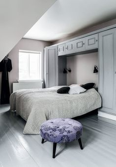 Delicate bedroom with a smart wardrobe cabinet over the kingsize bed.