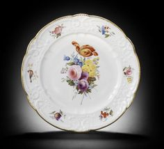A good Nantgarw plate of Brace service type, circa 1818-20. A good Nantgarw plate of Brace service type, circa 1818-20 Painted in London, probably in the Bradley workshop, with a full flower spray including a fine yellow and orange variegated tulip, the crisp C-scroll border reserving six panels painted with flower sprigs, a bird on a branch and an insect settled upon a bunch of redcurrants, gilt dentil rim, 25cm diam, impressed NANT-GARW CW