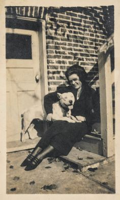 Woman sits with her pet pit bull dog