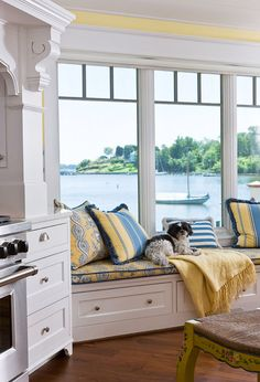 Window seat in the kitchen. Love the yellow throw and in the pillows. Yellow paint above the windows.