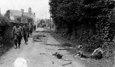 GIs belonging to the 35th Infantry Division pass by the remains of two German KIAs in the French village of Saint-Georges-Montcocq in the vicinity of Saint Lo. Note the panzerfaust (anti-tank weapon) by the foot of the KIA in the foreground. July 1944.