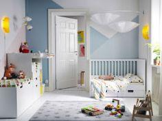 Chambre d'enfant meublée avec un lit bébé blanc avec deux tiroirs, une table à langer et un banc de rangement avec un grand tiroir sur roulettes.