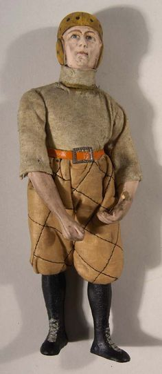 """ootball figural candy container c.1910-20. Very fine candy container in the shape of a period football player, which is depicted in full uniform with a dog eared style helmet, quilted pants, and miniature leather belt. The head is made of hand painted bisque porcelain with intricate detail. The arm joints are loose and there have been a few small repairs to the toe areas of the shoes. The body has also been adhered together at the neck where the candy receptacle is located. 9"""" tall"""