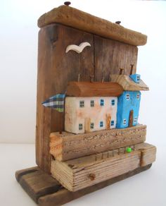 Turquoise A-top is based on an English harbour scene of three driftwood fishermens cottages built high above the promenade. With a line of railings and my trademark bead, it has several pieces of driftwood making the backdrop, and four more including the houses and roofs. The ceramic bird has been shaped and fired by me to add a finishing touch to this unique nautical accessory.  Overall measurements : It stands approximately 20cm high, 17.5cm wide and 8cm deep in miniature. The painted…