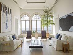 Dans le salon principal, deux canapés d'Axel Vervoordt se font face. On y trouve également des tableaux de Georg Baselitz (à gauche) et d'Alberto Burri (à droite), et la sculpture Kapuzenmann d'Erwin Wurm devant la fenêtre centrale. Des pièces vintage, tels les deux fauteuils de Giò Ponti et le lit de repos PK80 de Paul Kjaerholm, sont mariées à des tables d'appoint contemporaines, comme celles de gauche signées E15 et Nada Debs.