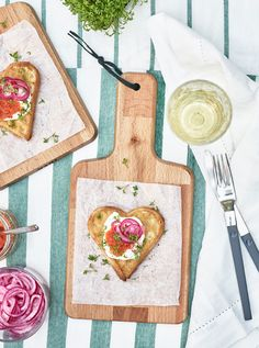 Recipe: Waffle hearts topped with caviar, creme fraiche and pickled red onion sit on small chopping boards.