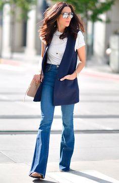 Lucy Whims atravessa a rua posando para foto de street style suando tshirt branca, calça jeans de cintura alta azul, sandália nude, colete azul, bolsa nude e óculos espelhados