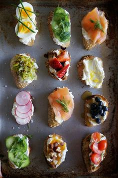 RICOTTA CROSTINI PARTY  Top Row: Hard Boiled Egg & Chives; Cucumber, Mint & Dill; Smoked Salmon & Dill***Second Row: Leeks Caramelized in Butter; Strawberries & Aged Balsamic Vinegar; Extra-Virgin Olive Oil, Lemon Zest & Sea Salt***Third Row: Radishes & Sea Salt; Smoked Salmon & Dill; Blueberries & Honey***Bottom Row: Cucumber, Mint & Dill; Hazelnuts & Apricot Jam; Tomatoes & Basil Pesto…