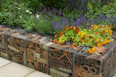 Gabion Walls of Recycled Material in Flower Garden - I wish they had a better photo cause this looks fantastic