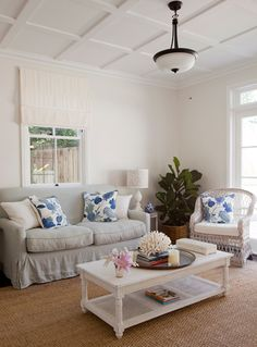 White with blue accents and a BIG PLANT! Love the plant basket n coral on the coffee table