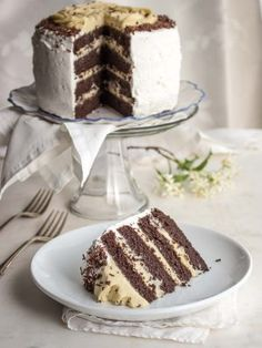 Low carb chocolate layer cake on a cake stand with a slice on a plate.