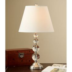 This antiqued 27-inch tall crystal table lamp will add light to any room. The four stacked graduated spheres and brushed nickel-finished base provide an alluring effect to this lamp. A cr��me-colored fabric shade is included.