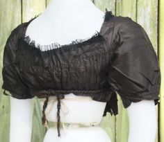 Ball gown bodice c. 1800 made of black China silk. Trimmed with fine black cotton net ruching and silk covered wooden buttons. Lined with brown cotton. The back is very narrow and the front crosses over and is secured, presumably by sewing it back in the day. Here, I have pinned it closed. There is a separate decorative front which covers the lining | eBay