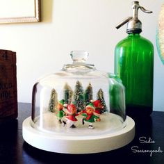 When I saw this cheese dome at the thrift store, I knew I could transform it into a winter/Christmas scene.and decided to be different by turning it into a sweet ice skating pond, straight out of an old postcard! Winter Christmas Scenes, Christmas Tree Angel, Christmas On A Budget, Christmas Bags, Christmas Themes, Christmas Tree Ornaments, Holiday Fun, Holiday Crafts, Christmas Decorations