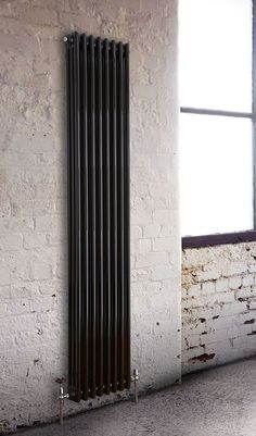 Traditional radiator in black. Stunning industrial loft apartment with brick walls. Windsor Traditional Black 3 Column Vertical Radiator by Best Heating.