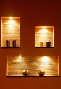 Contemporary lighting against a dramatic red painted wall. There are candles and recessed can lights in the rectangle wall niche. In each niche there is tan bamboo wallpaper. Click the image to see how much it costs to add recessed lighting.