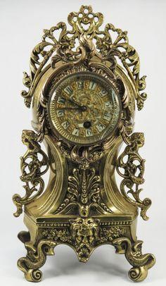 Relógio de mesa em bronze, com figuras mitológicas em suas alças, pés em formato de cobra, com cabeç