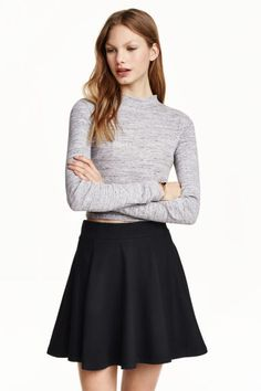 Klokkende rok: Een korte, klokkende rok van elastisch tricot met breed elastiek in de taille. Ongevoerd.