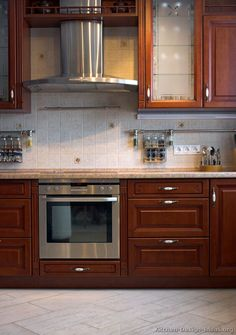 #Kitchen Idea of the Day: Cherry-Colored Kitchen with backsplash rail spice storage and a stainless steel hood.