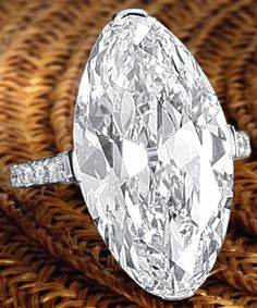 IMPORTANT DIAMOND RING.      Simply set with a modified marquise brilliant-cut diamond weighing 14.12 carats, to a mount set with brilliant-cut diamonds extending to the shoulders, mounted in platinum. Sotheby's.