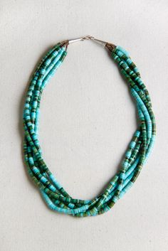 A mix of genuine green and blue Turquoise makes a great casual necklace. Like the green earth and blue sky entwined. This one will work well with every color of turquoise. The color combination and random arrangement make an eclectic statement. It is brought together with strands of pen shell heishi and sterling silver cones and clasp. Handmade in New Mexico.