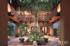 In this open interior courtyard, antique terracotta Parefeuille floor tile sets the scene for sky-high palm trees and antique metal stools shaped like mushrooms. The intricate mahogany, Balinese-style balcony grounds the space in exoticism.