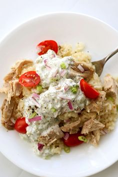 Instant Pot Smothered Greek Chicken and Rice--lemony bites of chicken and creamy rice with a generous scoop of deliciously light and refreshing yogurt-cucumber sauce, diced red onions and tomatoes on top.