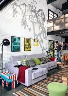 O morador Rodnei na janela. O grafite, de Bruno Dias, decora a parede atrás do sofá, da Gallery by Formato. Almofadas da Conceito Firma Casa. Da mesma loja são as malas e a luminária de piso. Manta Ralph Lauren e Tapete da Clatt