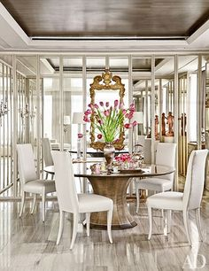 In the dining room, a Gracie wallpaper was used on the ceiling, and mirrored panels conceal storage for tableware; Solís Betancourt & Sherrill designed the table and chairs.