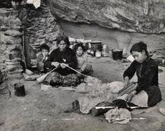 Navajo family processing sheep wool into yarn.  Circa 1940