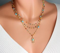 This is a stunning multi-layered necklace made with many colorful gemstones! Hand of Fatima, hamsa pendant is 18kt gold filled, measures 1 and has a Turquoise enamel center. These are faceted gemstones that measure 3-4mm in size . Gorgeous turquoise connector pendants are scattered on this necklace, making this necklace so unique! Necklace comes in three sizes, 16-18 , 18-20 or 20-22 with toggle closure. Comes nicely boxed, the perfect gift! Model has a small neck and is wearing a 16-18…