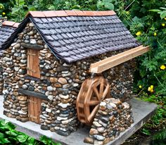 Enchanted Cottages created by Roger Davies:  This magnificent  model is built from pebbles and riverstone, with a traditional Welsh slate roof and hand-cut ridge tiles.  The doors, window, mill race and the wheel itself are fashioned from local oak.