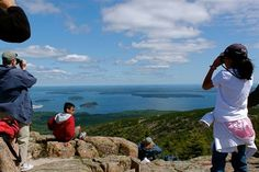 Hawk-watchers stand at the top of Cadillac Mountain to count and identify the migrating birds.