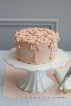 dusty rose cake with decorative tassel detail . . .