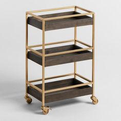 Modern and vintage styles meet in our sleek tiered rolling cart, crafted of walnut-toned wood and gold-finished metal. Outfitted with locking casters and three rectangular trays, it's an easy, elegant way to tidy up the bathroom, office or home bar. Barn Door Bookcase, Eclectic Desks, Chariot A Roulette, Home Office Accessories, World Market Store, Old Barn Doors, Bar Cart Decor, Storage Cart, Home Office Organization