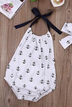 Simply adorable. Baby Romper. One of our top selling oufits. Romper + tie headband included. Nautical print for the little water lady. Soft cotton, comfy all day long. White with blue anchors. Find it in Lenny Lemons.