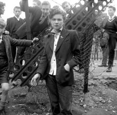1950, Teddy girl. Long trousers, long jacket, button up shirt, pinned up hair.