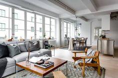 Loft de grandes ventales que demuestra que este tipo de viviendas se adaptan perfectamente a la decoración nórdica.