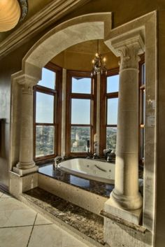 a whirlpool soaking tub is set into an alcove of windows, framed by columns, in this elegant master bathroom.