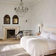 Enkelt sovrum med öppen spis och kristallkrona