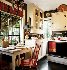 yes to the iron windows, yes to the tall wall cabinets, yes to the hardware and the rustic little table and (red!) chair