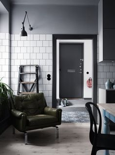 Vintage olive leather armchair in the corner of the kitchen of a sophisticated Swedish home in dark shades of grey and green - Kristofer Johnsson / Alexandra Ogonowski