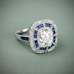 A stunning Antique Cushion Cut Diamond surrounded by a halo of diamonds and sapphires.