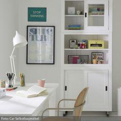 Weiße Möbel sind unaufdringlich und haben das Talent, sich in fast jeden Raum einfügen zu können. Der weiße Schreibtisch passt ideal zu dem hölzernen Wandschrank, welcher viel Platz zum Verstauen und Aufbewahren im Arbeitszimmer bereitstellt. Ein Arbeitszimmer mit weißen Möbeln zu gestalten, ist somit eine praktische Lösung, da der Schrank vor der weißen Wand wenig hervor sticht.