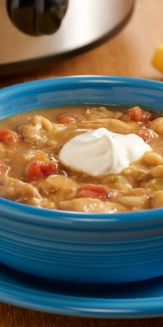 A slow cooker recipe for white chicken chili assembled quickly with chicken thighs, canned beans and zesty tomatoes.
