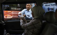 A woman exchanging money from her car at the Bank Indonesia Drive-Thru in Braga, Bandung, on July 23, 2012. The drive-through service was set up so people could exchange their money for small banknotes that are typically given as gifts during Ramadan and Idul Fitri. (JG Photo/Rezza Estily).