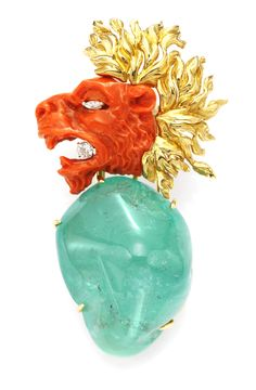 A  'Roaring Lion' Brooch, by Verdura. Designed With a 162.5cts Cabochon Emerald, Carved Coral, Textured Gold and Diamond.  Available at FD. www.fd-inspired.com