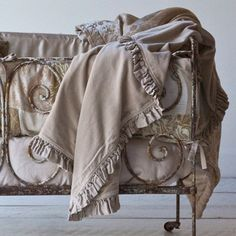 Bella Notte 100% cotton velvet baby blanket with a satin ruffle ... displayed in an antique iron crib